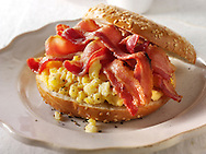 Crispy streaky bacon and scrambled eggs on a bagel
