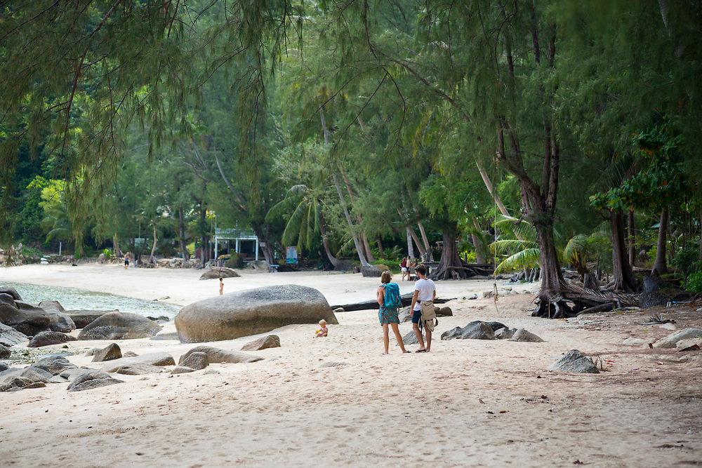 A young child plays in the sand as its parents look on during a visit to Haad Khom, a quiet beach on the north coast of Ko Phangan, Thailand. (July 2017)