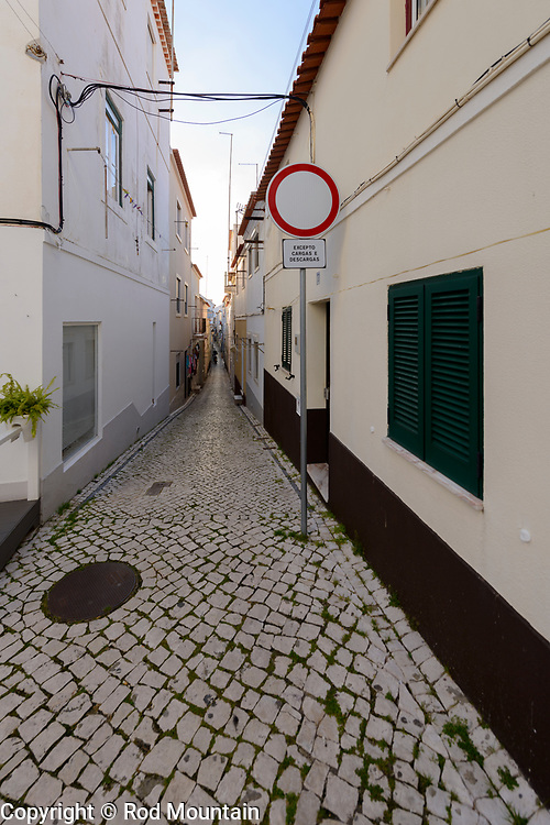 Nazaré, Portugal - February 12, 2018 - Nazaré Side Street 04 - An example of the streets and pathways in Nazaré leading towards the beach… very narrow! <br /> <br /> Image: © Rod Mountain<br /> http://www.rodmountain.com<br /> Nikon D800 / Nikkor Lens<br /> <br /> http://bit.ly/Nazaré_bw<br /> http://bit.ly/Nazare_Portugal<br /> https://www.visitportugal.com/en<br /> https://en.wikipedia.org/wiki/Nazaré,_Portugal<br /> http://www.cm-nazare.pt/en<br /> https://en.wikipedia.org/wiki/Portugal<br /> https://en.wikipedia.org/wiki/Portuguese_pavement <br /> <br /> @visitportugal @municipiodanazare<br /> <br /> @visitportugal @cmnazare @TurismodePortugal<br /> <br /> @visitportugal @CMNazareMata<br /> <br /> #Nazare #tourismportugal #portugal #visitportugal #culturaportugesa<br /> #storyofthestreets #timeless_streets #noirstreetlife #capturestreets #street #ig_europe #igworldclub #softcolors #urbanphotography #streetphotography#streetexploration #urbanandstreet #streetshared<br /> #theworldshotz#pixel_ig #photographyislifee#photographyislife #photographysouls <br /> #Europe #exploretheglobe #exploring