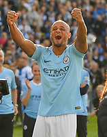 BRIGHTON, ENGLAND - MAY 12:  Vincent Kompany (4) of Manchester City celebrates in front of the City fans as he walks up to collect his winners medal and lift the Premier League trophy during the Premier League match between Brighton & Hove Albion and Manchester City at American Express Community Stadium on May 12, 2019 in Brighton, United Kingdom. (MB Media)