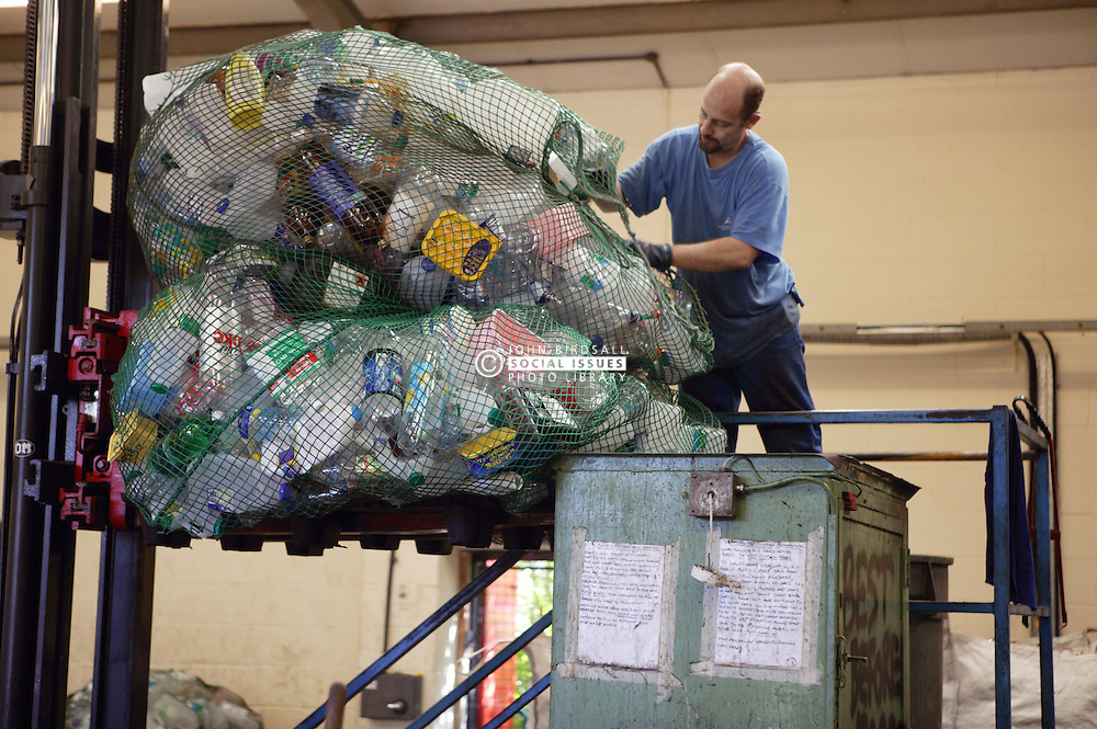 Man using baler machine to bale up plastic bottles for recycling,
