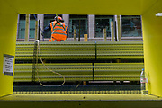 A construction workman supervises the lifting of materials, seen through a rectangular yellow site window, on 14th September 2017, in the City of London, England.