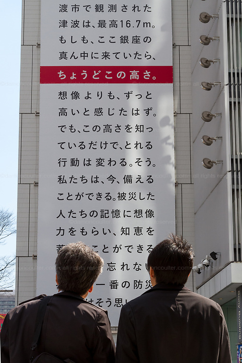 Two men look at a  large billboard on the side of the Sony Building in Ginza marks the sixth anniversary of the March 11th 2011 earthquake and tsunami in Tohoku. Ginza, Tokyo, Japan. Friday March 10th 2017 The billboard was created by Yahoo and shows the asks passers by to remember the disaster and the nearly 16,000 people who died. the line marked in red shows the maximum height of the tsunami (16.7 metres at Ofunato in Miyagi prefecture. The billboard is on display until March 12th.