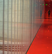 An individual walking on the red floor of Seattle's Central Public Library.  A spectacular building designed by Rem Koolhaas.