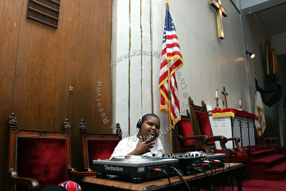 Ivan Bryan, 12, member of the Hip Hop Church Choir, is sitting at the mixer during a Mass Service at the Hip Hop Church in Harlem, New York, NY., on Thursday, June 29, 2006. A new growing phenomenon in the United States, and in particular in its most multiethnic city, New York, the Hip Hop Church is the meeting point between Hip Hop and Christianity, a place where ëGodí is worshipped not according to religious dogmatisms and rules, but where the ëHoly Spirití is celebrated by the community through young, unique, passionate Hip Hop lyrics. Its mission is to present the Christian Gospel in a setting that appeals to both, those individuals who are confessed Christians, as well as those who are not regularly attending traditional Services, while helping many youngsters from underprivileged neighbourhoods to feel part of a community, to make them feel loved and to help them not to give up when problems arise. The Hip Hop Church is not only forward-thinking but it also has an important impact where life at times can be difficult and deceiving, and where young people can be easily influenced for the worst purposes. At the Hip Hop Church, members are encouraged to sing, dance and express themselves in any way that the ëSpirit of Godí moves them. Honours to students who have overcome adversity, community leaders, church leaders and some of the unsung pioneers of Hip Hop are common at this Church. Here, Hip Hop is the culture, while Jesus is the centre. Services are being mainly in Harlem, where many African Americans live; although the Hip Hop Church is not exclusive and people from any ethnic group are happily accepted and involved with as much enthusiasm. Rev. Ferguson, one of its pioneer founders, has developed ëHip-Hop Homileticsí, a preaching and worship technique designed to reach the children in their language and highlight their sensibilities, while bringing forth Christianity. This ëKeep It Realí evangelism style is the centrepiece of Rev. Fergusonís ministry, one t