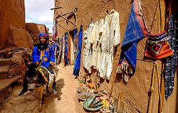 A local man in traditional costume rides a donkey in Aït Benhaddou, Morocco. Aït Benhaddou is an ighrem (fortified village), situated along the former caravan route between the Sahara and Marrakech in present-day Morocco. There are four families still living in the ancient village. Inside the walls of the ksar are half a dozen (Kasbahs) or merchants houses and other individual dwellings, and is a great example of Moroccan earthen clay architecture.<br /> <br /> Aït Benhaddou has been a UNESCO World Heritage Site since 1987.<br /> <br /> (c) Andrew Wilson   Edinburgh Elite media