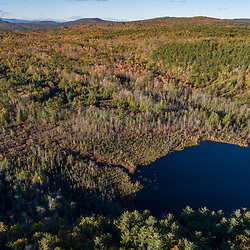 Drone view of  forest Coldrain Pond and in New Durham, New Hampshire.