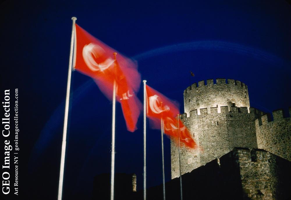 Flags fly near floodlit battlements of ancient fortress.