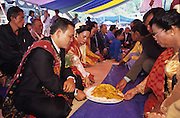 Bride and groom eating traditional meal during christian wedding near Lake Toba..Batak Indigenous Christian people living on Samosir Island and nearby Lake Toba in Indonesia. There are some 6 million Christian Batak in Indonesia, the world's largest Muslim country of 237 million people, which has more Muslims than any other in the world. Though it has a long history of religious tolerance, a small extremist fringe of Muslims have been more vocal and violent towards Christians in recent years. ..Batak religion is found among the Batak societies around Lake Toba in north Sumatra. It is ethnically diverse, syncretic, liable to change, and linked with village organisations and the monotheistic Indonesian culture. Toba Batak houses are boat-shaped with intricately carved gables and upsweeping roof ridges, and Karo Batak houses rise up in tiers. Both are built on piles and are derived from an ancient Dong-Son model. The gable ends of traditional houses, Rumah Bolon or Jabu, are richly decorated with the cosmic serpent Naga Padoha carved in wood or in mosaic, lizards, double spirals, female breasts, and the head of the singa, a monster with protruding eyes that is part human, part water buffalo, and part crocodile or lizard. The layout of the village symbolises the Batak cosmos. They cultivate irrigated rice and vegetables. Irrigated rice cultivation can support a large population, and the Toba and the Karo live in densely clustered villages, which are limited to around ten homes to save farming land. The kinship system is based on marriage alliances linking lineages of patrilineal clans called marga. In the 1820's Islam came to the southern Angkola and Mandailing homelands, and in the 1850's and 1860's Christianity arrived in the Angkola and Toba region with Dutch missionaries and the German Rheinische Mission Gesellschaft. The first German missionary caused the Dutch to stop Batak communal sacrificial rituals and music, which was a major blow to the traditional religion.