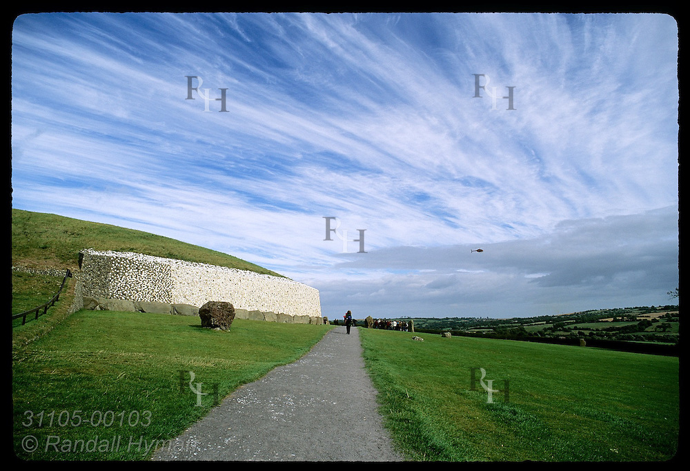 Distant woman walks up path to Newgrange burial mound, a Neolithic (3200 BC) passage grave in Boyne Valley; County Meath, Ireland.
