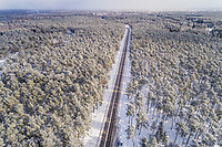 Aerial view of an empty straight road in the forest of Naage in Estonia.