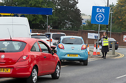 © Licensed to London News Pictures 08/10/2021.<br /> Sidcup, UK, A member of staff directing cars. Motorists queuing for fuel at Tesco's petrol station in Sidcup, South East London. The petrol shortage continues in London and the South East with retailers calling for an inquiry into the fuel crisis. Photo credit:Grant Falvey/LNP
