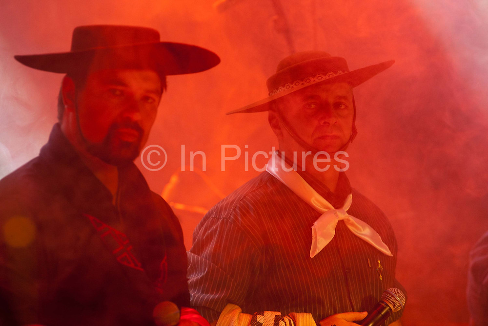 Brazilian Gaucho men in traditional dress on stage, with smoke and lighting effects in foreground, dramatic red lighting. Reponte da Cancao music festival and song competition in Sao Lorenzo do Sul, RIo Grande do Sul, Brazil.