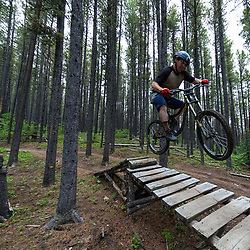 Hitting a jump on Race of Spades at Moose Mountain in Alberta, Canada