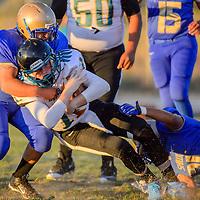 Navajo Prep Eagle quarterback Dakota Halliburton (11) is brought down as he rushes through the Zuni Thunderbird defense Friday at Zuni High School.