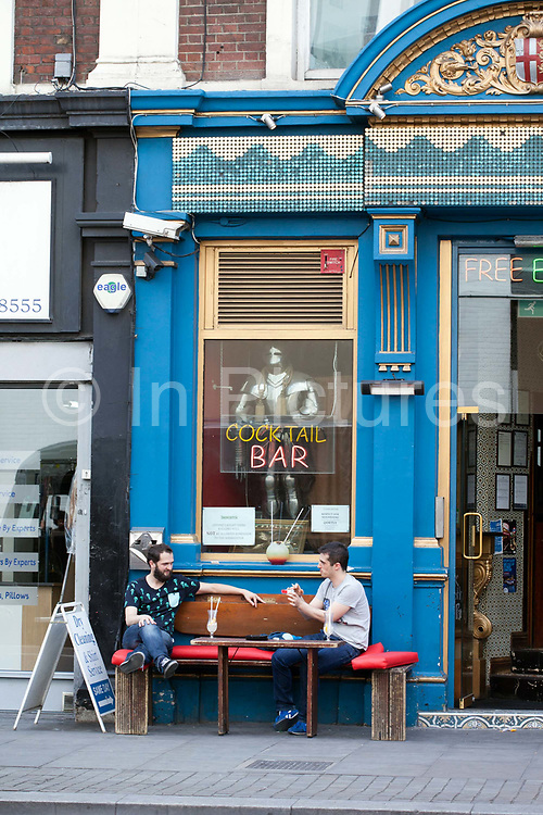 Men drink and socialise outside a bar in Shoreditch, London<br /> Shoreditch, an area that was dominated by light industry is now home to cafes and fashionable restaurants and cafes