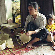 A young girl sits with her mother while she weaves baskets, Luu Thuong, 'Te' grass weaving village, Ha Tay province, Vietnam. With Vietnam's growing population making less land available for farmers to work, families unable to sustain themselves are turning to the creation of various products in rural areas.  These 'craft' villages specialise in a single product or activity, anything from palm leaf hats to incense sticks, or from noodle making to snake-catching. Some of these 'craft' villages date back hundreds of years, whilst others are a more recent response to enable rural farmers to earn much needed extra income.