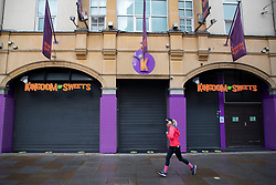 © Licensed to London News Pictures. 08/11/2020. London, UK. A woman jogs past a shuttered branch of Kingdom of Sweets near Leicester Square, Central London. A national lockdown has been put in place in an attempt to fight a second wave of the COVID-19 strain of Coronavirus. Photo credit: George Cracknell Wright/LNP