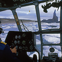 Cape Tegethoff, Hall Island, Franz Josef Land, Russia. A helicopter pilot flies by sea stacks in the Arctic Ocean.
