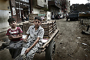 """Young's  """"Zabbaleen"""" collector in a Mokattam street with his carriage.On the outskirts of Cairo in the middle of Manshiet Nasr neighborhood is located Mokattam settlement known as """"Garbage City"""" is inhabited by Zabbaleen, a community of about 45,000 Coptic Christians living for decades to recycle waste generated by the Egyptian capital: plastic, aluminum, paper and organic waste transformed into compost. Most part of the Association for the Protection of the Environment (APE), an NGO that works in the area, whose objectives are to protect the environment and improve the livelihoods of garbage scavengers in Cairo. According to the UN, the work is done in Mokattam is one of the ten best examples of world environmental improvement. El Cairo , Egipt, June 2011. ( Photo by  Jordi Camí )."""