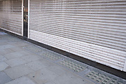 Souvenir shops and small businesses remain closed and shutters down in the West End on 25th June 2020 in London, England, United Kingdom. As the July deadline approaces and government will relax its lockdown rules further, the West End remains quiet, while some non-essential shops are allowed to open with individual shops setting up social distancing systems.