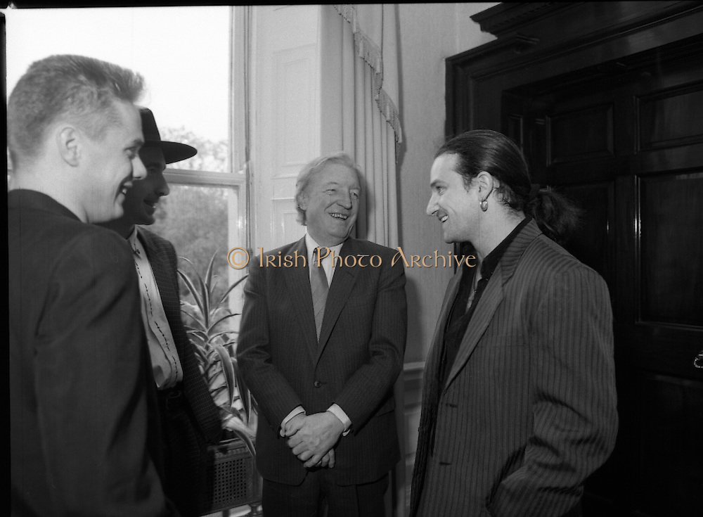 U2 Meet An Taoiseach, Charles Haughey.    (R58)..1987..18.05.1987..05.18.1987..18th May 1987..After their highly successful tour of America, An Taoiseach, Charles Haughey welcomed U2 back to Ireland with a reception held in Iveagh House, Dublin. Iveagh House formerly a home to the Guinness family is now held by the Department of Foreign Affairs...U2 and An Taoiseach pose for the cameras; (L-R),.Larry Mullen, 'The Edge' (Dave Evans),Charles Haughey and 'Bono' (Paul Hewson).