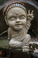 Smiling Buddha statue making a peace sign, along the Road to Hana, Maui, Hawaii
