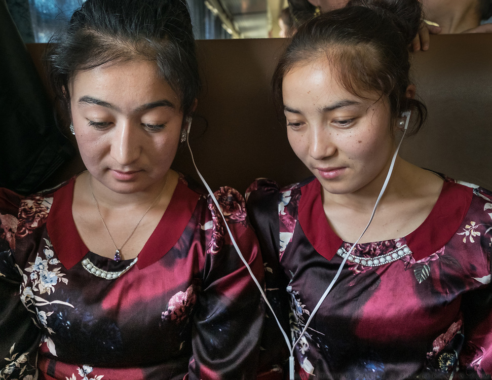 Gul Bostan and Nur Biye, two students from the Hotan university go for a visit to Kashgar for exams. They watch a turkish movie on their phone. Uighur speak a Turkic language. Life inside the train - mostly Muslim Uighur people  ride this train.