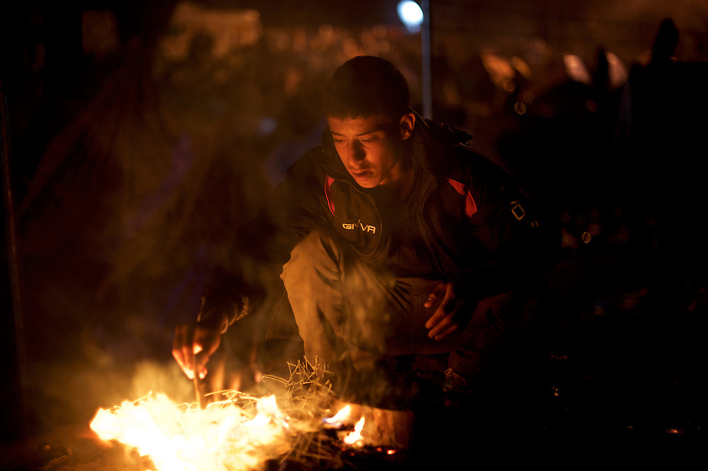 A Syrian refugee prepares a fire to cook some food on the train tracks near the border between Greece and Macedonia in Idomeni, Greece. Around 13,000 migrants and refugees, mostly from the Middle East and African nations, are believe to be stranded here awaiting a chance to proceed their journey towards Germany and other northern European countries.