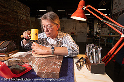 Ute Jaeckel of Hamburg, Germany works her fine leather art in the Intermot Customized Hall during the Intermot International Motorcycle Fair. Cologne, Germany. Thursday October 4, 2018. Photography ©2018 Michael Lichter.