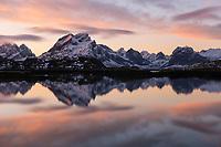 Mountain peaks of Moskenesøy reflect in fjord at sunrise, Lofoten Islands, Norway