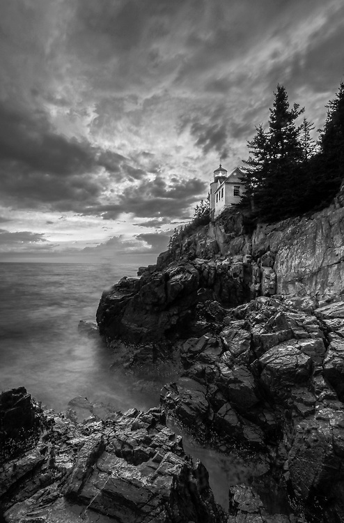 Black and White New England photography of the iconic Bass Harbor Head Light located on Mount Desert Island within Maine Acadia National Park on the southeast corner of MDI. The lighthouse towers over the swirling Atlantic Ocean and seacoast, marking the entrance to Bass Harbor and Blue Hill Bay. It is one of the most iconic scenery of Acadia NP as Bass Harbor Light is dramatically located on the edge of rugged cliffs.<br /> <br /> This New England B&W lighthouse fine art photography image is available as museum quality photography prints, canvas prints, acrylic prints or metal prints. Fine art prints may be framed and matted to the individual liking and decorating needs:<br /> <br /> https://juergen-roth.pixels.com/featured/cliffside-bass-harbor-head-lighthouse-juergen-roth.html<br /> <br /> Good light and happy photo making!<br /> <br /> My best,<br /> <br /> Juergen<br /> Prints: http://www.rothgalleries.com<br /> Photo Blog: http://whereintheworldisjuergen.blogspot.com<br /> Instagram: https://www.instagram.com/rothgalleries<br /> Twitter: https://twitter.com/naturefineart<br /> Facebook: https://www.facebook.com/naturefineart