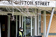 A Police officer is seen at the main entrance to 12 Sutton Street amid a full and total lockdown of 9 housing commission high rise towers in North Melbourne and Flemington during COVID-19 on 5 July, 2020 in Melbourne, Australia. After 108 new cases where uncovered overnight, the Premier Daniel Andrews announced on July 4 that effective at midnight last night, two more suburbs have been added to the suburb by suburb lockdown being Flemington and North Melbourne. Further to that, nine high rise public housing buildings in these suburbs have been placed under hard lockdown for a minimum of five days, effective immediately.  Residents in these towers will not be allowed to leave their units for any reason. Police will be stationed at every entry and exit point, every level, and they will also surround these locations preventing any movement in, or out. There is a total of 1354 units and over 3000 residents living in these buildings including the states most vulnerable people. These new restrictions will remain in place for fourteen days with fears of further lockdowns to come. The Government have stressed that if Victorians do not follow the basic COVIDSafe rules, the whole state will go back in to lockdown. (Image by Dave Hewison/ Speed Media)