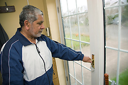 Older man checking that the front door is locked,