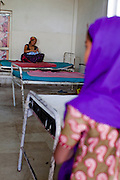 A young girl looks on as Amrita Rokya (left), 18, cradles her 2-day-old baby in the Bardia District Hospital, one hour's walk from her village in Bardia, Western Nepal, on 29th June 2012. In Bardia, StC works with the district health office to build the capacity of female community health workers who are on the frontline of health service provision like ante-natal and post-natal care, and working together against child marriage and teenage pregnancy especially in rural areas. Photo by Suzanne Lee for Save The Children UK