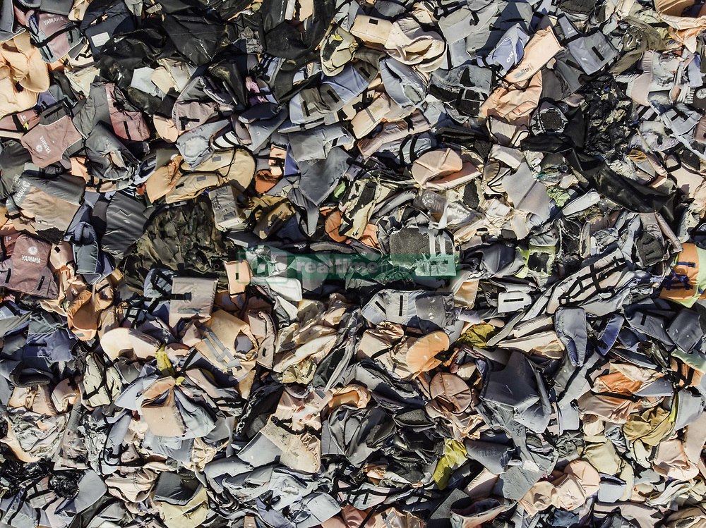 July 8, 2018 - Greece - Drone images of faded lifejackets, rubber rings an pieces of the rubber dinghies left by refugees are making a mountain pile in Molyvos village, near Eftalou beach, arrival or landing spot of boats full of refugees from Turkey. There was an estimation about 500.000 life jackets in that place. Lesvos has been a hot spot for refugees. July 13, 2018 - Lesvos island, Greece  (Credit Image: © Nicolas Economou/NurPhoto via ZUMA Press)