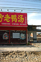"""China, Beijing, Chaoyang, San Jian Fang, 2008. View of a restaurant protesting forcible eviction by using """"death"""" wreaths, traditionally reserved for funerals. Superstition may have prevented authorities from demolishing this building.."""