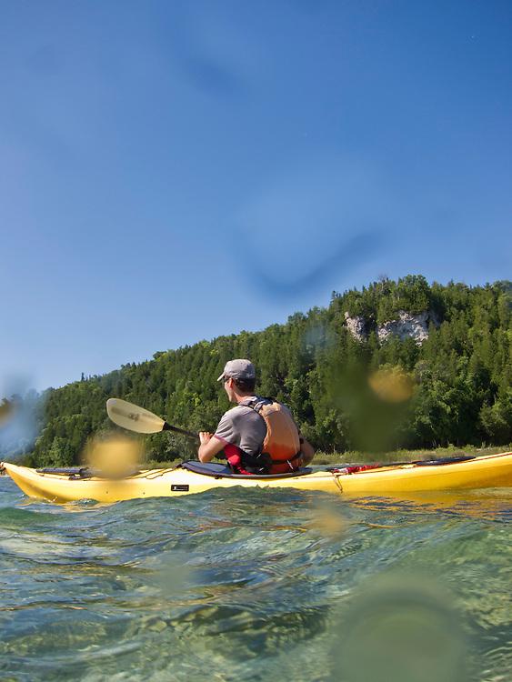 A kayaker explores the shoreline of Mackinac Island Michigan on Lake Huron.