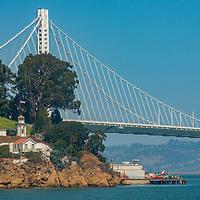 California's  San Francisco Bay Bridge rises behind an old lighthouse on Yerba Buena Island.