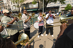 Washington DC; USA: Dupont Circle area, noted for its fountain, street musicians, bookstores, shops, embassies, and brick houses.  Street musicians, wind ensemble, mainly trombonists, performing..Photo copyright Lee Foster Photo # 21-washdc79607