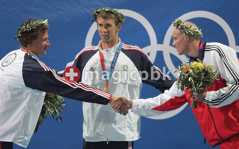 US swimmer Michael Phelps (C) sporting his gold medal, has silver medalist Ryan Lochte from the USA (L) and bronze medalist George Bovell from Trinidad and Tobago shake hands after the men's 200m Individual Medley Final at the Athens Olympic Aquatic Centre, Thursday, 19 August 2004.         (Photo by Patrick B. Kraemer / MAGICPBK)