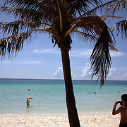 An asian tourist takes photographs at White Beach on October 3, 2008 in Boracay Island, the Philippines. Photo Tim Clayton..Asian tourists at White Beach, Boracay Island, the Philippines...The 4 km stretch of White beach on Boracay Island, the Philippines has been honoured as the best leisure destination in Asia beating popular destinations such as Bali in Indonesia and Sanya in China in a recent survey conducted by an International Travel Magazine with 2.2 million viewers taking part in the online poll...Last year, close to 600,000 visitors visited Boracay with South Korea providing 128,909 visitors followed by Japan, 35,294, USA, 13,362 and China 12,720...A popular destination for South Korean divers and honeymooners, Boracay is now attracting crowds of tourists from mainland China who are arriving in ever increasing numbers. In Asia, China has already overtaken Japan to become the largest source of outland travelers...Boracay's main attraction is 4 km of pristine powder fine white sand and the crystal clear azure water making it a popular destination for Scuba diving with nearly 20 dive centers along White beach. The stretch of shady palm trees separate the beach from the line of hotels, restaurants, bars and cafes. It's pulsating nightlife with the friendly locals make it increasingly popular with the asian tourists...The Boracay sailing boats provide endless tourist entertainment, particularly during the amazing sunsets when the silhouetted sails provide picture postcard scenes along the shoreline...Boracay Island is situated an hours flight from Manila and it's close proximity to South Korea, China, Taiwan and Japan means it is a growing destination for Asian tourists... By 2010, the island of Boracay expects to have 1,000,000 visitors.