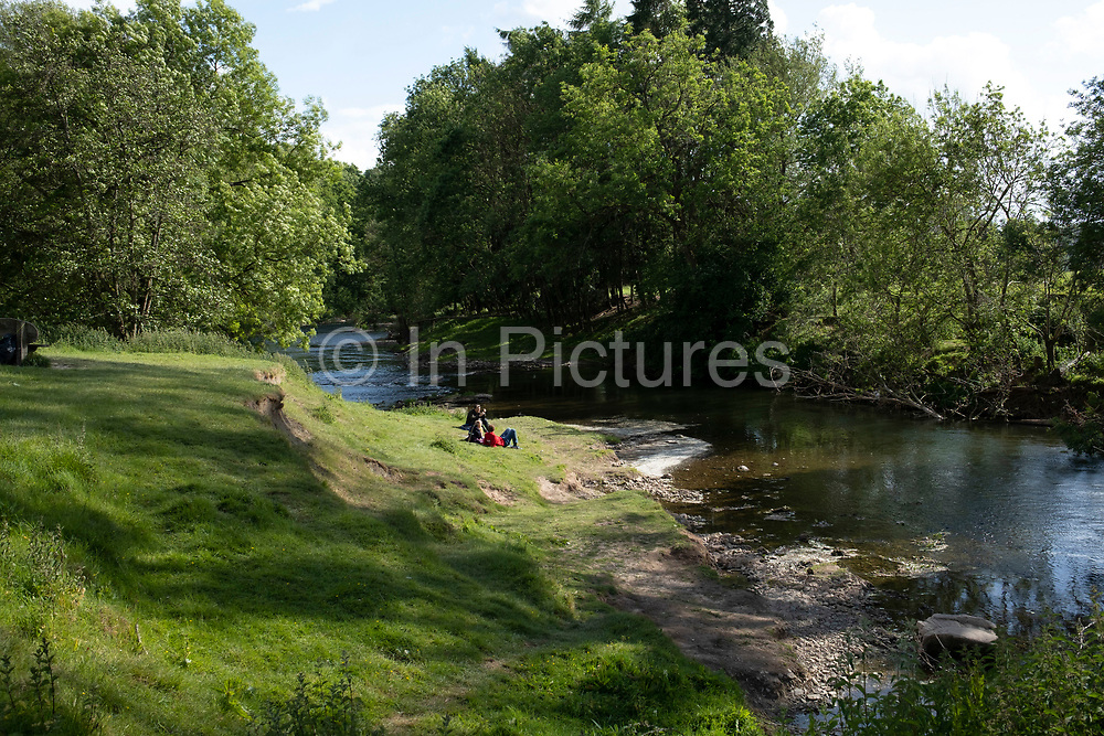 Family sits beside the River Teme on 23rd May 2020 near Martley, United Kingdom. Martley is a village and civil parish in the Malvern Hills district of the English county of Worcestershire. The River Teme rises in Mid Wales, and flows through into England down to Shropshire and Worcestershire. The whole of the River Teme was designated as an SSSI, by English Nature, in 1996.