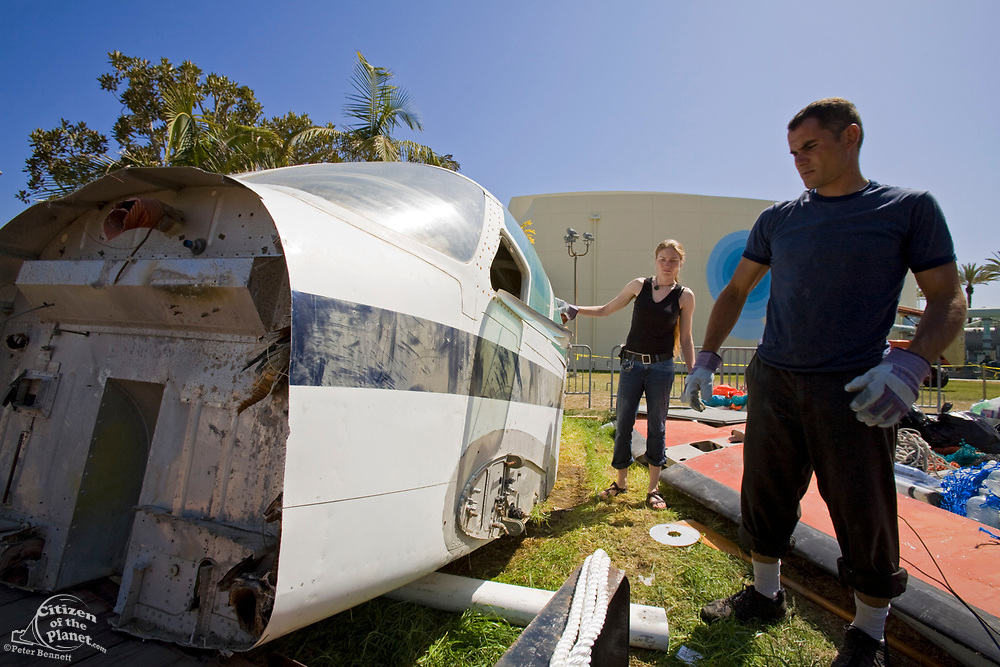 """Agilita's Dr. Marcus Eriksen and Holly Gray get ready to move the plane's fuselage to the Junk raft. in the Summer of 2008, the raft called """"Junk""""  will sail 2,100 miles from Los Angeles through the North Pacific Gyre, on raft made of junk. Designed by Dr. Marcus Eriksen and Joel Paschal, the raft, dubbed """"Junk"""" will be constructed from 20,000 plastic bottles, an airplane fuselage, discarded fishing nets, a solar generator, and a bicycle generator. Long Beach, California, USA"""