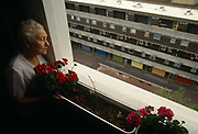 An elderly lady resident of a tower block, watches the outside world from her high-rise window, overlooking the Middlesex Estate in the City of London. A window box with geraniums is by the glass and she peeers down to a bleak urban estate, empty of human contact or friendly neighbours. She lives alone in this grim place but she is looking after herself showing brushed hair , a lace top and lipstick. The world outside is a depressingly empty landscape of concrete walkways and garage doors, an inner-city environment devoid of human interaction or friendliness.