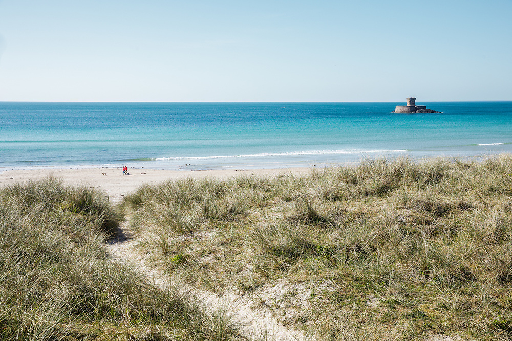 Views from up on the sand dunes of the landmark La Rocco Tower, the calm, crystal clear turquoise water of St Ouen's Bay and a couple walking their dog in Jersey, CI