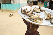 A girl carries dried fish she intends to sell on a plate sitting on her head in the village of Popoko, Bas-Sassandra region, Cote d'Ivoire, on Sunday March 4, 2012.