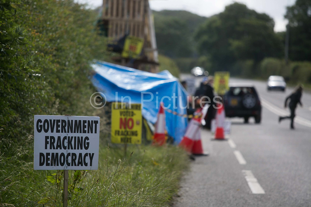 A sign put up by anti-fracking activists near the entrance to  Quadrillas drill site in New Preston Road, July 01 2017, Lancashire, United Kingdom. Government fracking democracy.The blockade is a repsonse to the emmidiate drilling for shale gas, fracking, by the fracking company Quadrilla and part of an ongoing struggle where makeshift towers and makeshift camps have sprung up outside the premisses. Lancashire voted against permitting fracking but was over ruled by the conservative central Government. All the activists have been active in the struggle against fracking for years but this is their first direct action of peacefull protesting. Fracking is a highly contested way of extracting gas, it is risky to extract and damaging to the environment and is banned in parts of Europe . Lancashire has in the past experienced earth quakes blamed on fracking.
