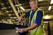 "A British Airways baggage handler scans the bar code of his airline passenger's item of luggage before loading it into the aircraft hold container bins. 50-70,000 pieces of BA baggage a day travel through 11 miles of conveyor belts which were installed in a 5-storey underground hall beneath the 400m (a quarter of a mile) length of Terminal 5 at Heathrow Airport. T5 alone has the capacity to serve around 30 million passengers a year and was completed in 2008 at a cost of £4.3bn. The system was designed by an integrated team from the airport operator BAA, BA and Vanderlande Industries of the Netherlands, and handles both intra-terminal and inter-terminal luggage. From writer Alain de Botton's book project ""A Week at the Airport: A Heathrow Diary"" (2009)."