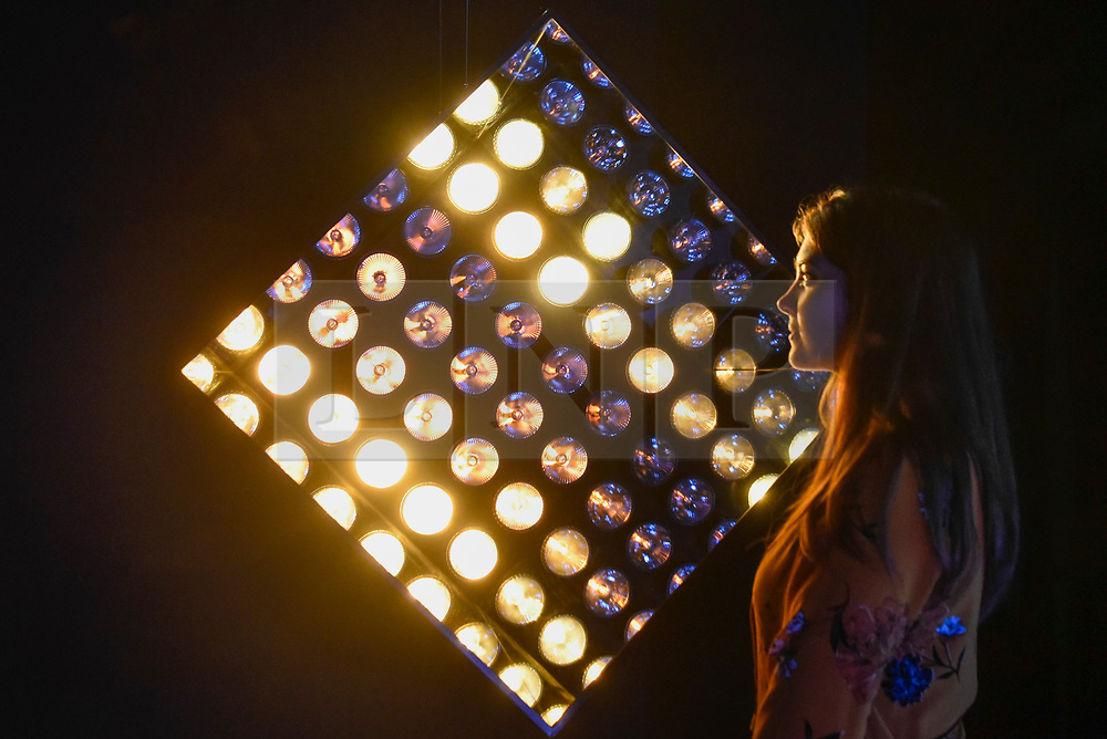 """© Licensed to London News Pictures. 27/10/2019. LONDON, UK. A staff member poses next to looping stress test of light and sound called """"J3RR1. A Planned Torture"""",  2017, by NONE Collective.  Advance preview of """"24/7: A Wake-Up Call For Our Non-Stop World"""", a new exhibition opening on 31 October at Somerset House.  The show examines our inability to switch off from our 24/7 culture.  Over 50 multi-disciplinary works explore the pressure to produce and consume information around the clock. taking visitors on a 24-hour cycle from dawn to dusk through interactive installations.  Photo credit: Stephen Chung/LNP"""